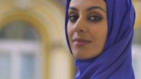 Portret van jonge mooie gelukkig moslimvrouw met doordrongen camera bekijken en neus die, glimlachen stock video