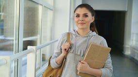 Portret van jonge mooie Kaukasische zekere vrouwelijke student status in witte glazige gang die positief glimlachen stock footage