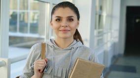 Portret van jonge mooie Kaukasische zekere vrouwelijke student status in witte glazige gang die positief glimlachen stock videobeelden