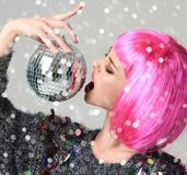 Portret van jonge mooie maniervrouw die in modieuze roze vleugel met de discobal van de Kerstmisdecoratie knipogen stock foto's