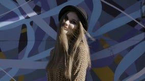 Portret van jonge mooie modieuze vrouw met het zwarte hoed stellen op blauwe graffityachtergrond actie Het model dragen stock video