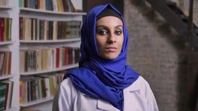Portret van jonge mooie moslimvrouw die in hijab camera met ernstige uitdrukking bekijken stock footage