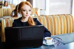 Portret van jonge mooie onderneemsters die van koffie genieten tijdens het werk aangaande draagbare laptop computer Stock Fotografie