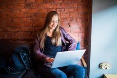Portret van jonge mooie onderneemsters die van koffie genieten tijdens het werk aangaande draagbare laptop computer, die het vrou Stock Afbeelding