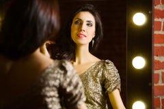 Portret van jonge mooie sexy vrouw status dichtbij spiegel met stock foto's
