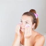 Portret van jonge mooie vrouw die haar gezicht schoonmaken Royalty-vrije Stock Afbeeldingen