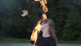 Portret van jonge mooie vrouw die in masker een show met vlam voor bomen uitvoeren Bekwame fireshowkunstenaar stock video