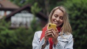 Portret van jonge mooie vrouw gebruikend app op smartphone, glimlachend en texting op mobiele telefoon Vrouw die in het rood drag stock video