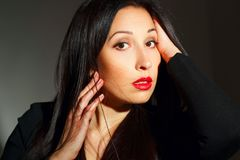 Portret van jonge mooie vrouw met rode lippenstift over donkere bedelaars stock foto's