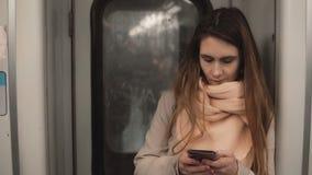 Portret van jonge mooie vrouw status in metro Smartphone van het meisjesgebruik, doorbladert Internet in metro trein stock video