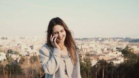 Portret van jonge mooie vrouw status op het panorama van Rome, Italië Wijfje die op smartphone spreken Stock Afbeeldingen