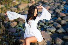Portret van jonge mooie vrouw in witte kleding op rotsachtig strand stock foto