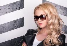 Portret van jonge mooie vrouw in zwarte leerjasje en sunglases Stock Afbeelding