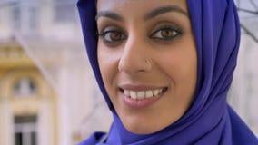 Portret van jonge moslimvrouw in de paraplu van de hijabholding en het glimlachen bij camera, mooi wijfje met doordrongen neus stock video