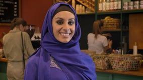 Portret van jonge moslimvrouw in hijab die zich in koffie bevinden en bij camera, charmante dame met doordrongen neus glimlachen stock footage