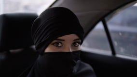 Portret van jonge, moslimvrouw met ogenmake-up met in zwarte niqab of burqa, die in de auto op de achterbank zitten - stock videobeelden