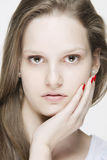 Portret van jonge natuurlijke kijkende vrouw wat betreft haar gezicht met haar hand Stock Foto's