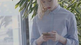 Portret van jonge onderneemster, die bericht op haar smartphone in heldere zaal, langzame motie typt stock footage