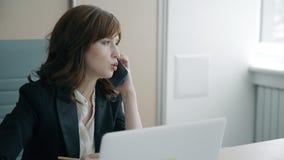 Portret van jonge onderneemster die op telefoon in haar privé-kantoor spreken stock videobeelden