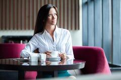 Portret van jonge schitterende vrouwelijke het drinken thee en het kijken met glimlach uit het venster van de koffiewinkel terwij stock foto