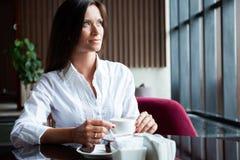 Portret van jonge schitterende vrouwelijke het drinken thee en het kijken met glimlach uit het venster van de koffiewinkel terwij stock foto's