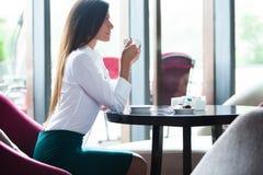 Portret van jonge schitterende vrouwelijke het drinken thee en het kijken met glimlach uit het venster van de koffiewinkel terwij stock afbeelding