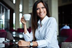 Portret van jonge schitterende vrouwelijke het drinken thee en het kijken met glimlach uit het venster van de koffiewinkel terwij stock afbeeldingen