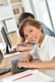 Portret van jonge schooljongen in klaslokaal stock foto