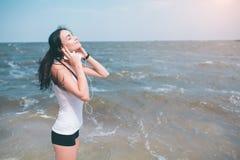 Portret van jonge sportieve vrouw die in hoofdtelefoons terwijl het zitten dichtbij oceaan in de zomer, het aantrekkelijke vrouwe stock fotografie
