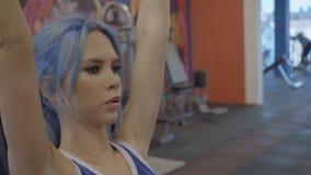 Portret van jonge sportvrouw, die gezette domoorpers in de gymnastiek doet stock videobeelden