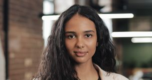 Portret van jonge succesvolle onderneemster op bezig kantoor Knappe vrouwelijke werknemer die camera en het glimlachen bekijken stock video