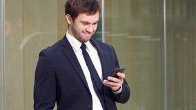 Portret van jonge succesvolle zakenman gebruikend smartphone en bekijkend camera in modern bureau stock video