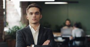 Portret van jonge succesvolle zakenman op bezig kantoor Knappe mannelijke werknemer die camera bekijken en duimen omhoog binnen d stock footage