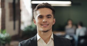 Portret van jonge succesvolle zakenman op bezig kantoor Knappe mannelijke werknemer die camera en het glimlachen bekijken Zaken stock videobeelden