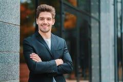 Portret van jonge succesvolle zekere zakenman in de stad op de bureaubouw achtergrond Mens in pak stock afbeeldingen