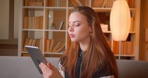 Portret van jonge tiener die in tabletzitting op bank op boekenrekken achtergrondhorloges in camera thuis zoeken stock videobeelden