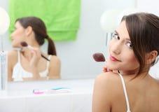 Portret van jonge volwassen vrouw die rouge toepast Stock Afbeeldingen
