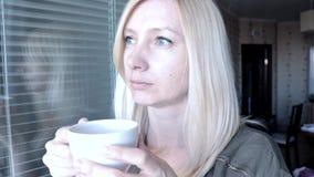 Portret van jonge vrij aantrekkelijke blonde vrouw met blauwe ogen die zich dichtbij het open venster in de ochtend, het drinken  stock video
