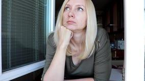 Portret van jonge vrij aantrekkelijke blonde vrouw met blauwe ogen die zich dichtbij het open venster in de ochtend, het kijken b stock videobeelden