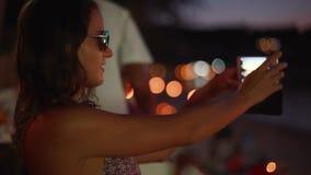 Portret van jonge vrij donkerbruine vrouw in zonnebril die makend gezichten die selfie foto nemen die smartphone gebruiken met st stock footage