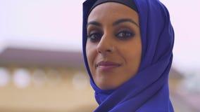 Portret van jonge vrij moslimvrouw die in hijab camera, mooi wijfje met doordrongen neus bekijken stock video