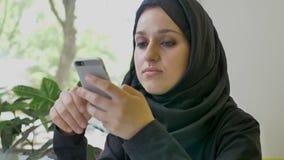 Portret van jonge vrij moslimvrouw in hijabzitting in koffie, op telefoon typen en bepaald holdingstelefoon die, die denken stock footage