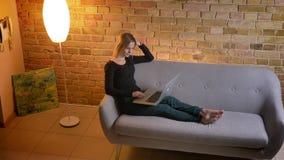 Portret van jonge vrij vrouwelijke op een film op laptop letten en huisvrouw die cheerfully terwijl het zitten op glimlachen stock videobeelden