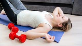Portret van jonge vrouw ademhaling nauwelijks na het uitoefenen op vloer bij woonkamer royalty-vrije stock afbeelding