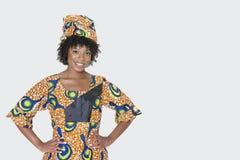 Portret van jonge vrouw in Afrikaanse drukkledij die zich met handen op heupen over grijze achtergrond bevinden royalty-vrije stock afbeelding