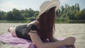 Portret van jonge vrouw in de de zomer witte hoed die op het strand liggen Het concept van de de zomervrije tijd Weekendtijd Mooi stock videobeelden