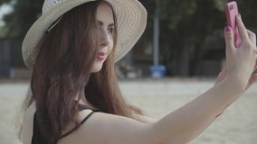 Portret van jonge vrouw in de de zomer witte hoed die selfie op haar cellphone nemen die op het strand rusten De vrije tijd van d stock footage