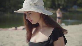 Portret van jonge vrouw in de de zomer witte hoed op het strand Mensen die bij de rivier op de achtergrond rusten De zomer stock footage