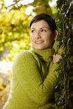 Portret van jonge vrouw die aan boomboomstam leunt Royalty-vrije Stock Fotografie