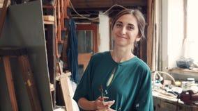 Portret van jonge vrouw die een canvas in een studio schilderen stock video